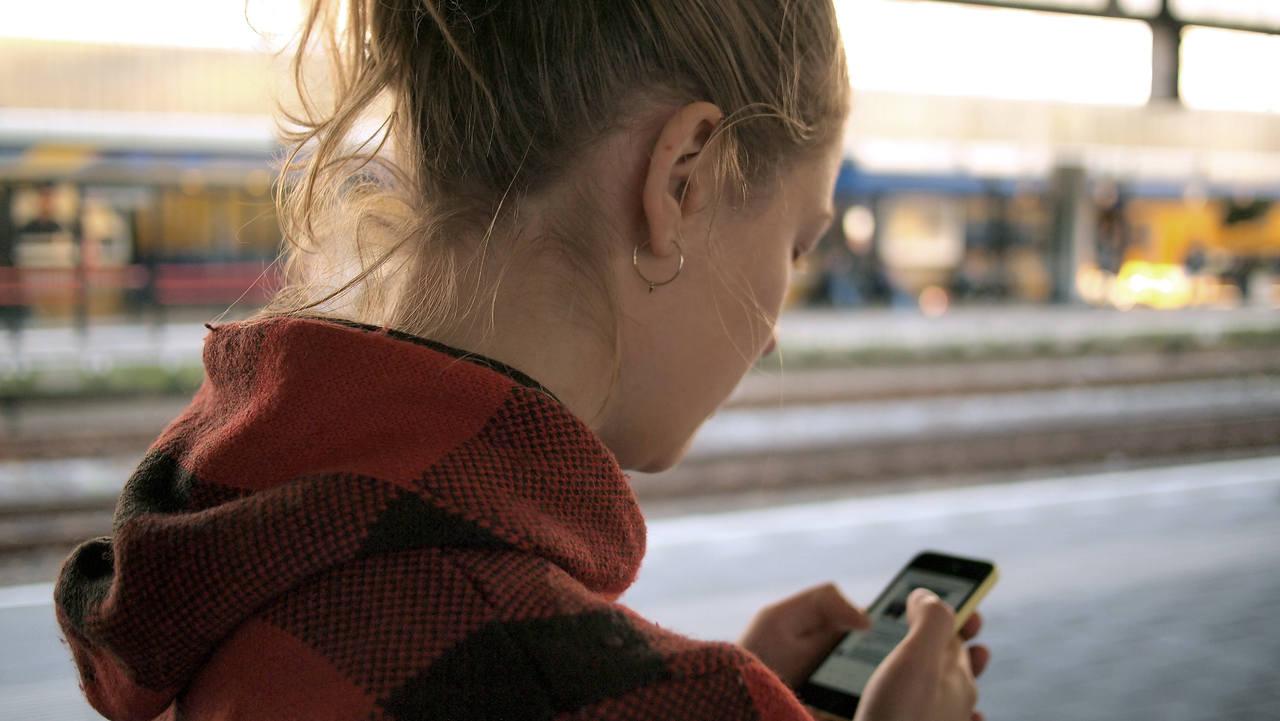 mulher loira de agasolho vermelho mexe no celular enquanto aguarda metro