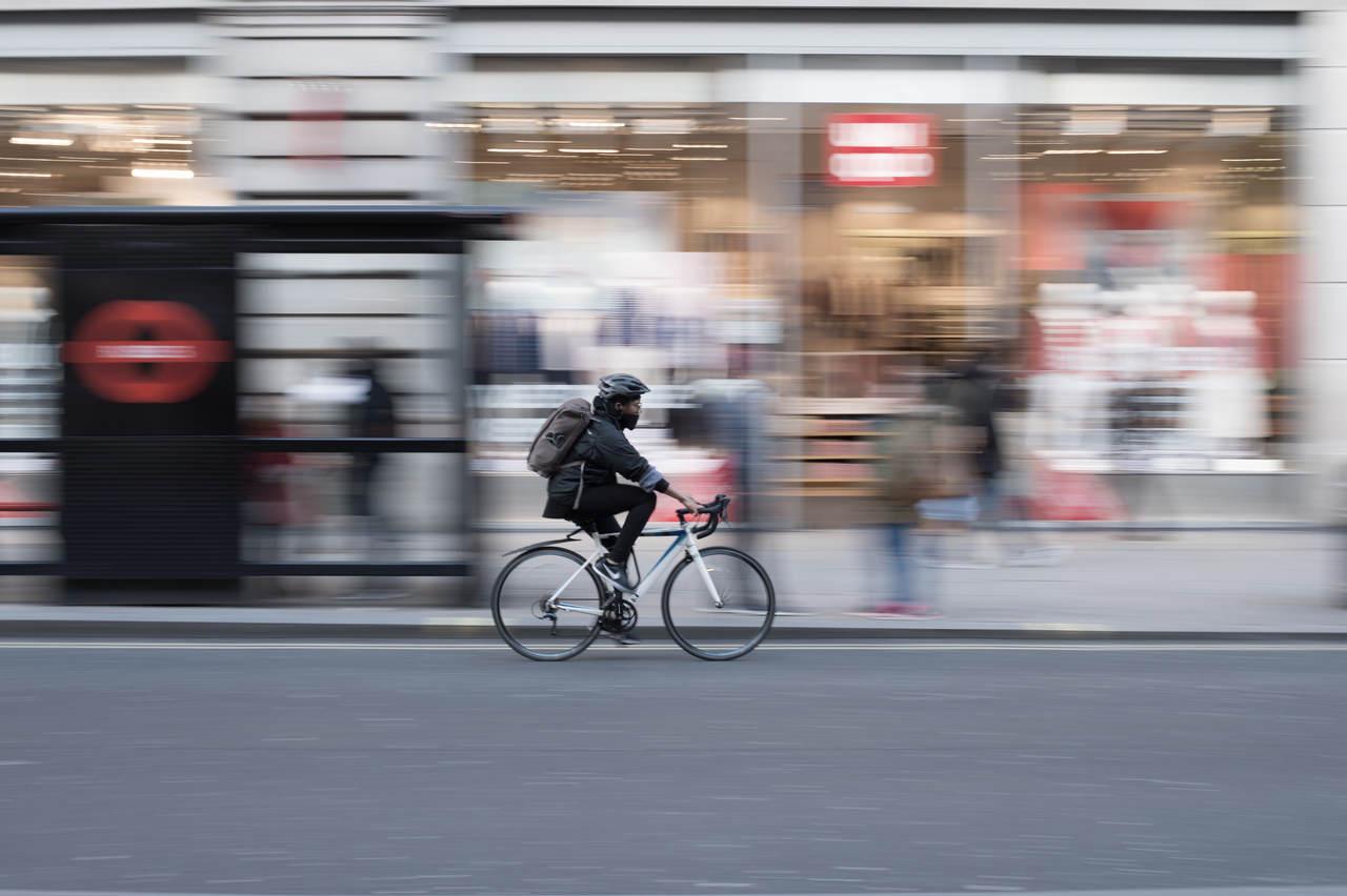 ciclista agasalhada pedalando nas ruas de londres
