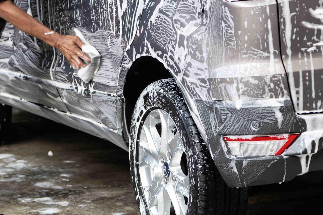 carro ensaboado sendo lavado com espuma e bucha automotiva