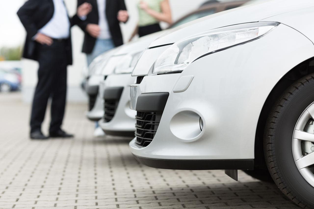 vendedor encontra clientes para venda de carro branco