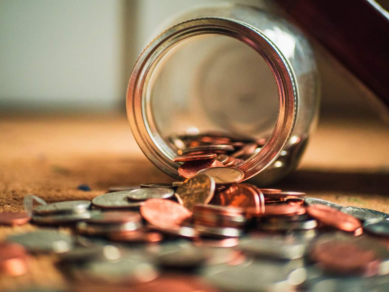 pote cofrinho de moedas aberto com moedas espalhadas sob a mesa