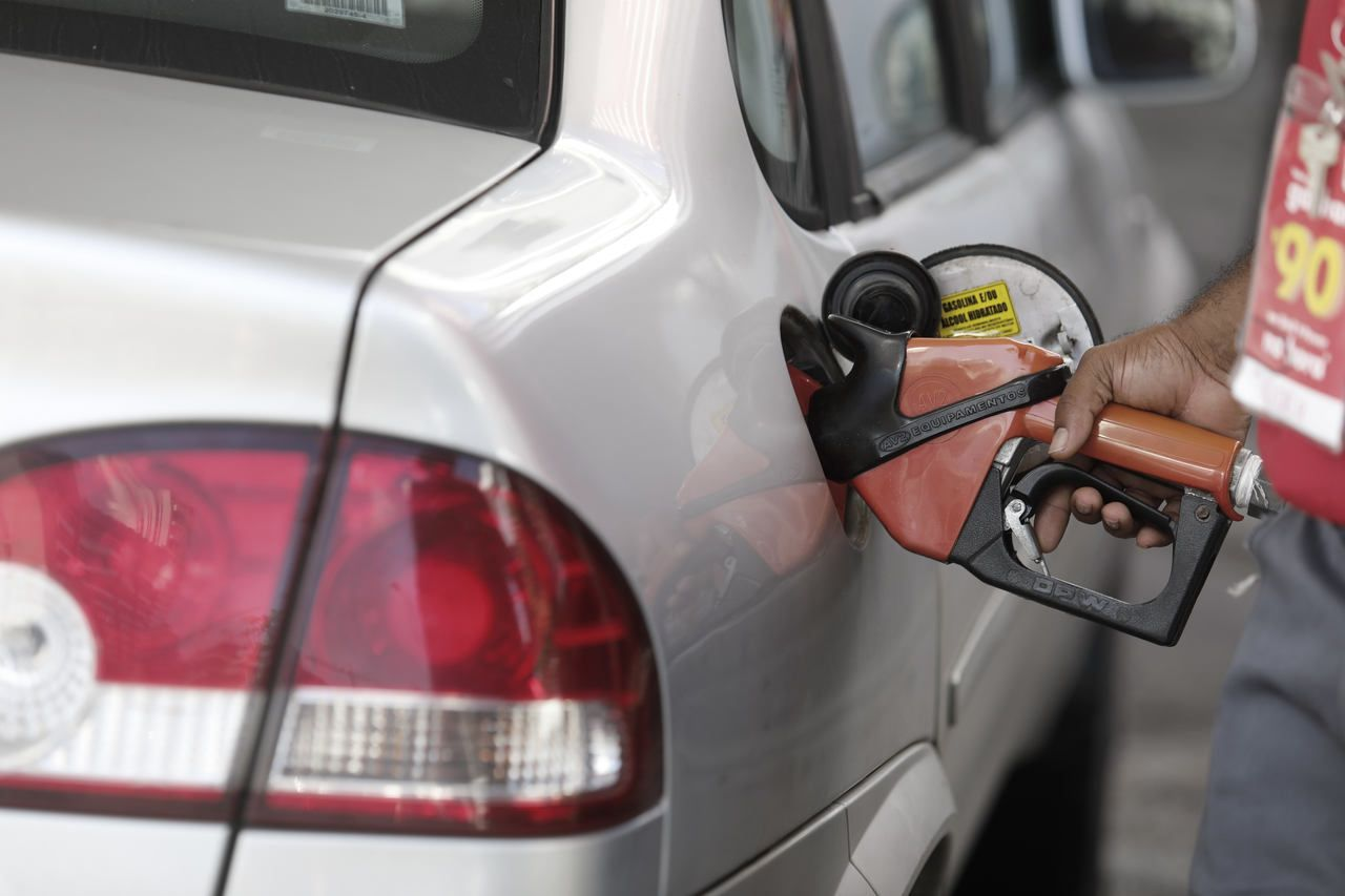 carro sedan cinza sendo abastecido em posto de gasolina