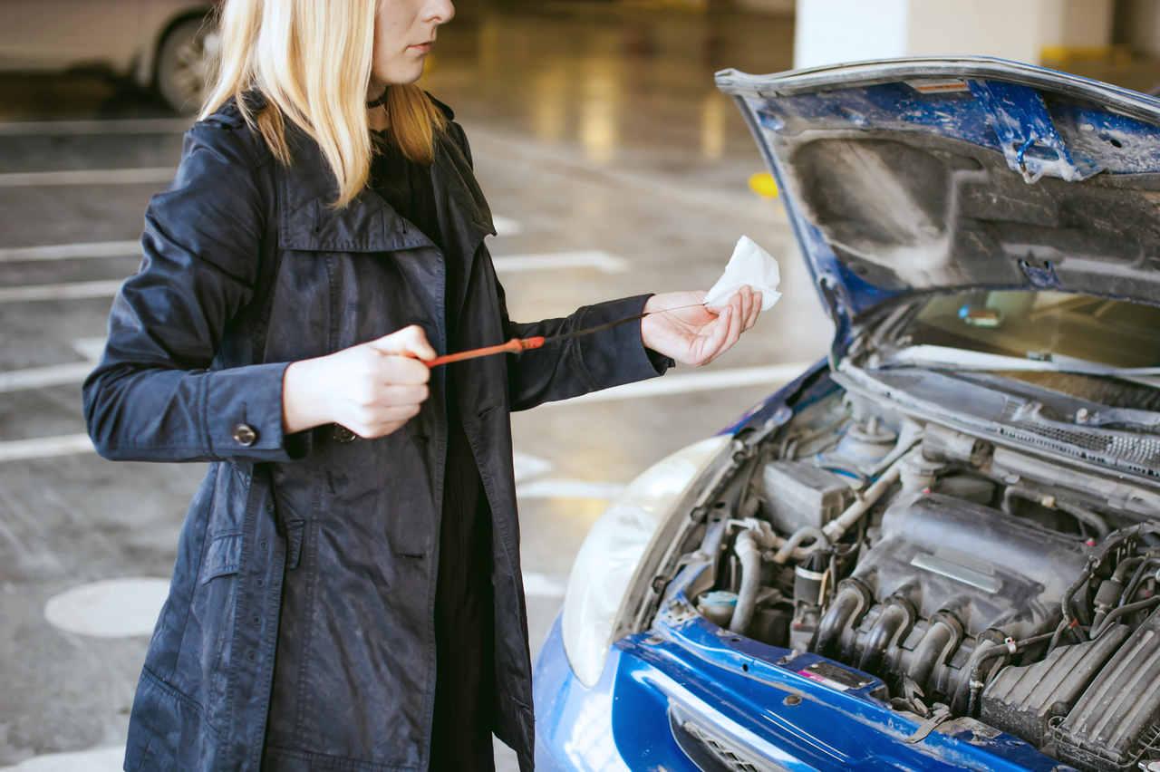 mulher checa o nível do óleo do motor do seu carro